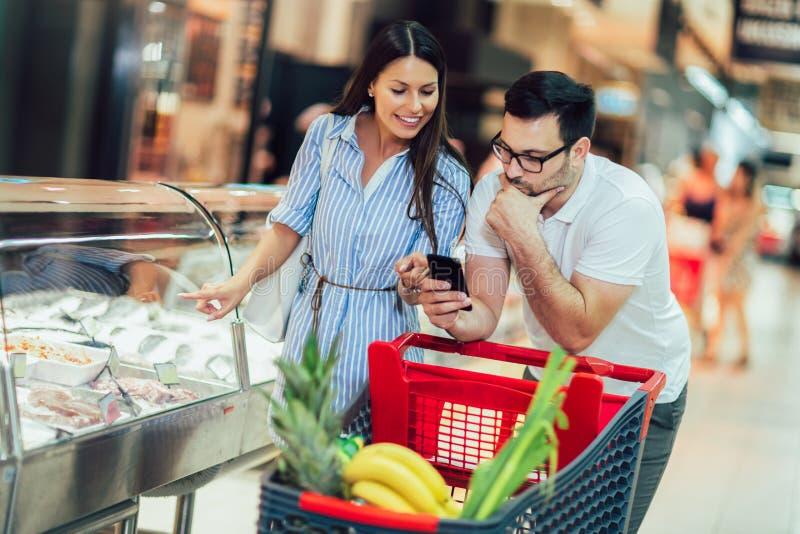 Pares jovenes que enlazan el uno al otro y que sonríen mientras que camina mientras que camina en tienda de alimentación con el c imagenes de archivo