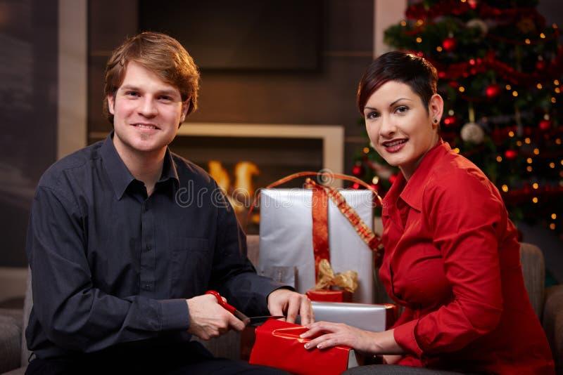 Pares jovenes que envuelven los regalos de la Navidad imagenes de archivo