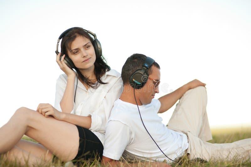 Pares jovenes que escuchan la música imagen de archivo libre de regalías