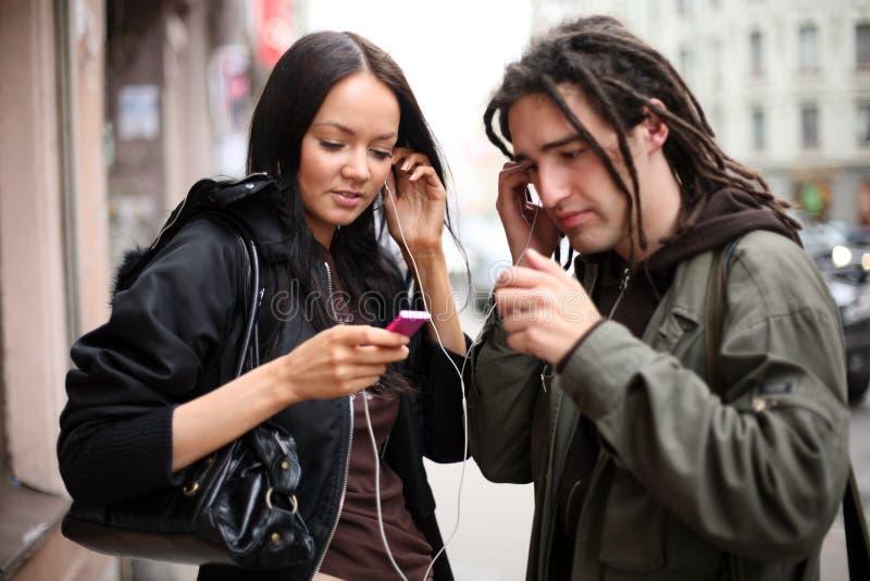 Pares jovenes que escuchan la música imagen de archivo
