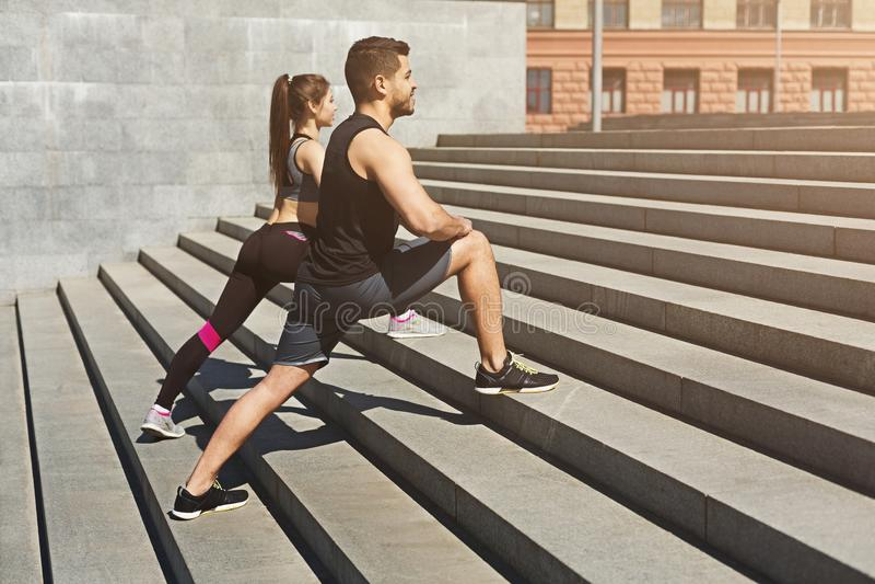 Pares jovenes que estiran las piernas en el ambiente urbano fotos de archivo