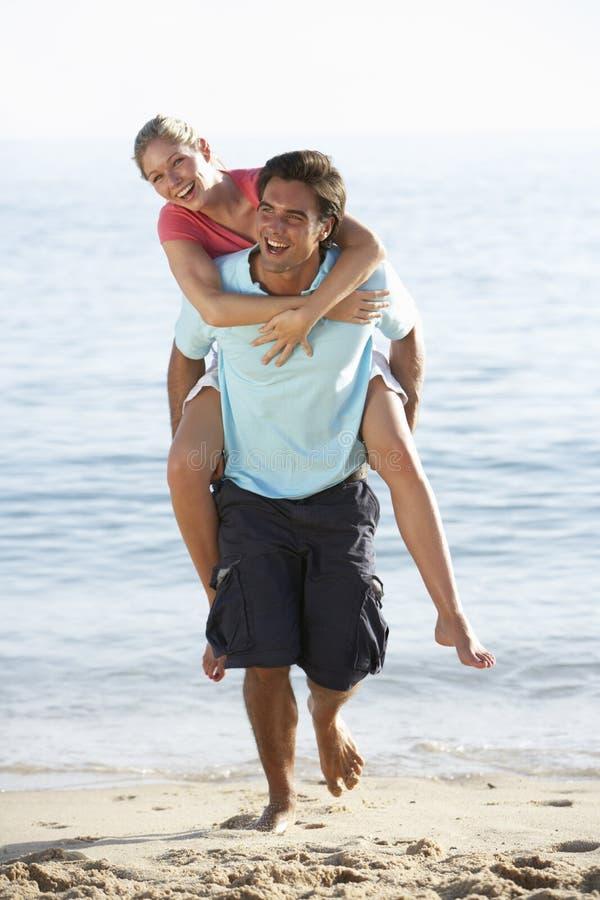 Pares jovenes que gozan a cuestas el día de fiesta de la playa foto de archivo