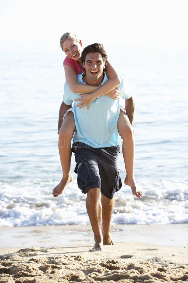 Pares jovenes que gozan a cuestas el día de fiesta de la playa imagen de archivo