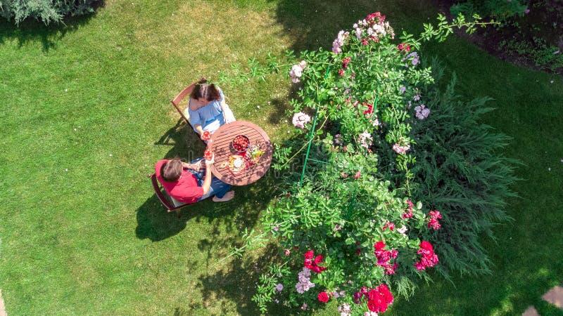 Pares jovenes que gozan de la comida y del vino en jardín de rosas hermoso en fecha romántica, la opinión superior aérea desde ar imágenes de archivo libres de regalías