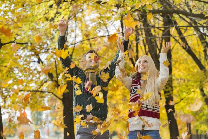 Pares jovenes que gozan de las hojas de otoño que caen en parque imagen de archivo libre de regalías