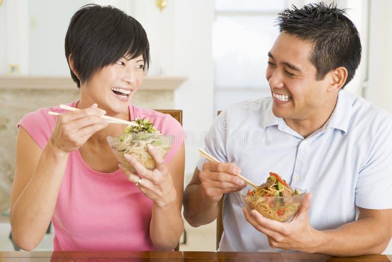 Pares jovenes que gozan del alimento chino foto de archivo