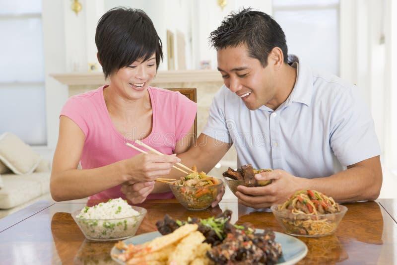 Pares jovenes que gozan del alimento chino fotografía de archivo