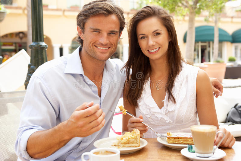 Pares jovenes que gozan del café y de la torta imágenes de archivo libres de regalías
