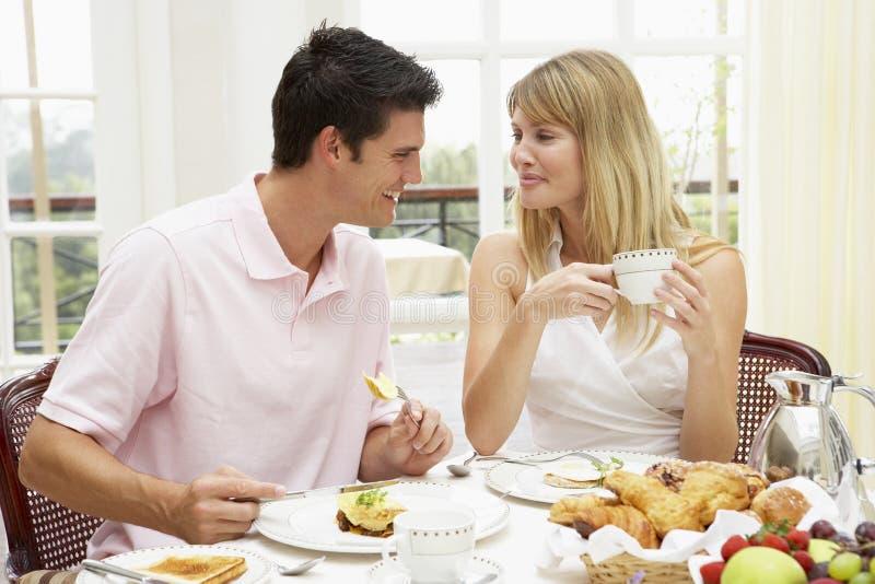 Pares jovenes que gozan del desayuno del hotel foto de archivo