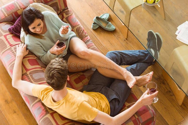 Pares jovenes que gozan del vino rojo en el sofá imagen de archivo