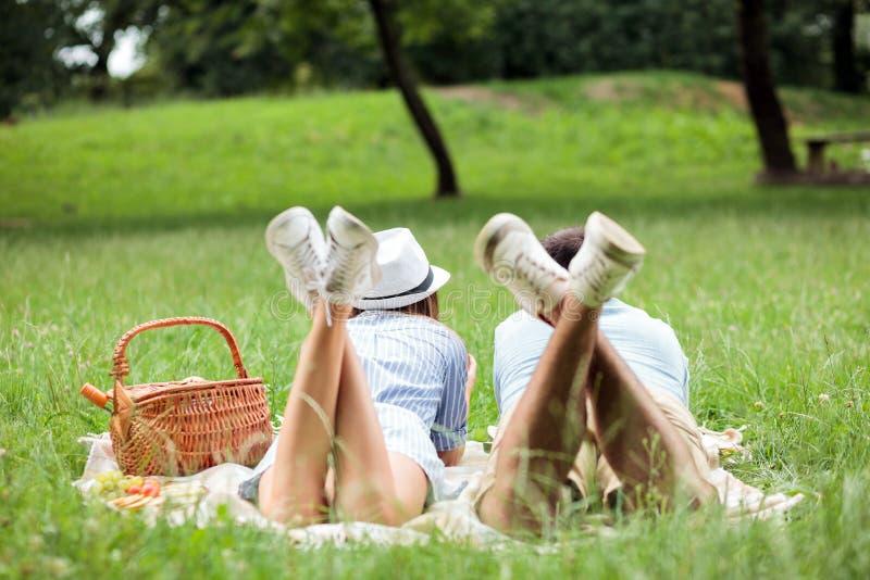Pares jovenes que gozan relajando tiempo de la comida campestre en un parque, mintiendo en una manta de la comida campestre fotos de archivo libres de regalías