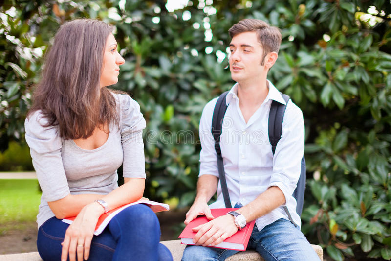 Pares jovenes que hablan al aire libre foto de archivo