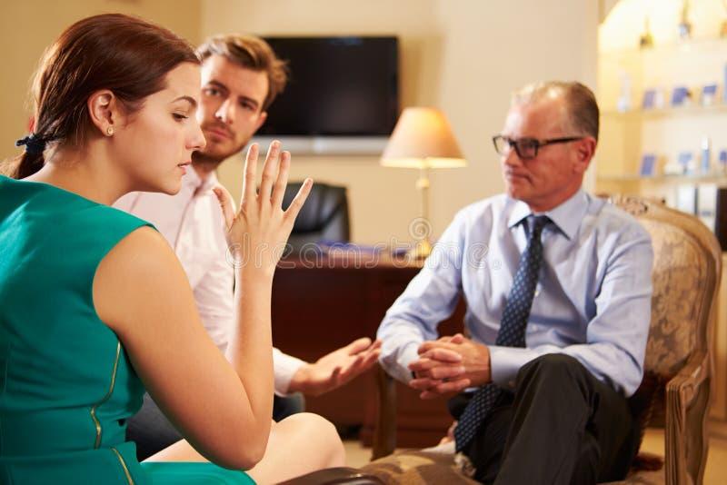 Pares jovenes que hablan con el consejero de sexo masculino imagen de archivo libre de regalías