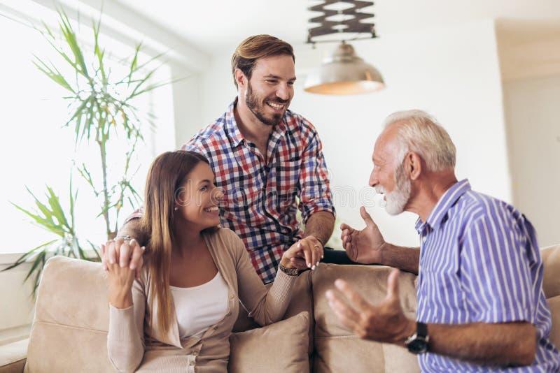 Pares jovenes que hablan con su padre mayor foto de archivo