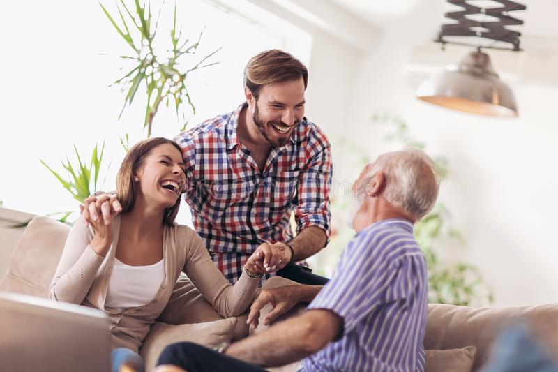 Pares jovenes que hablan con su padre mayor imagen de archivo