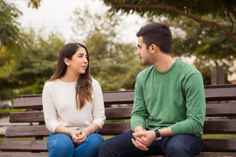 Pares jovenes que hablan en un parque foto de archivo