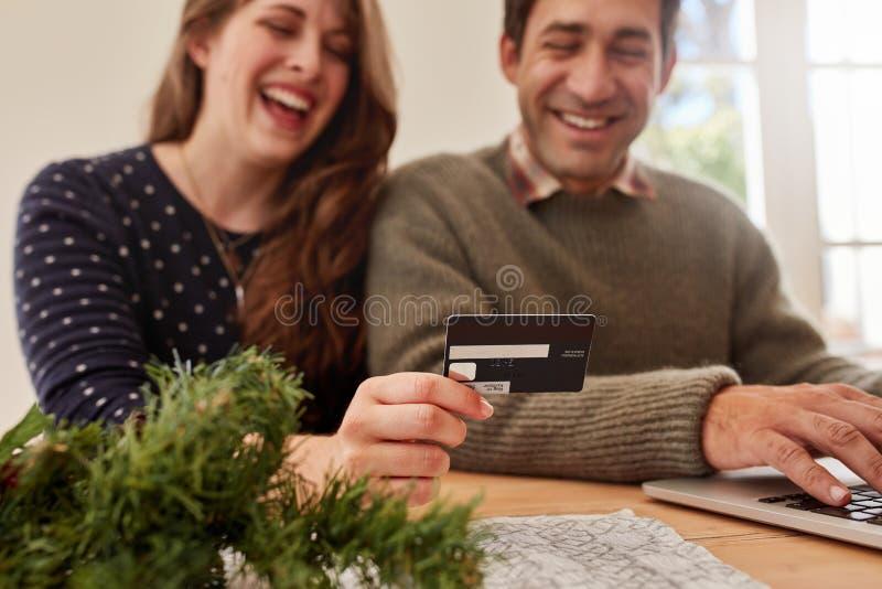 Pares jovenes que hacen compras en línea para la Navidad foto de archivo