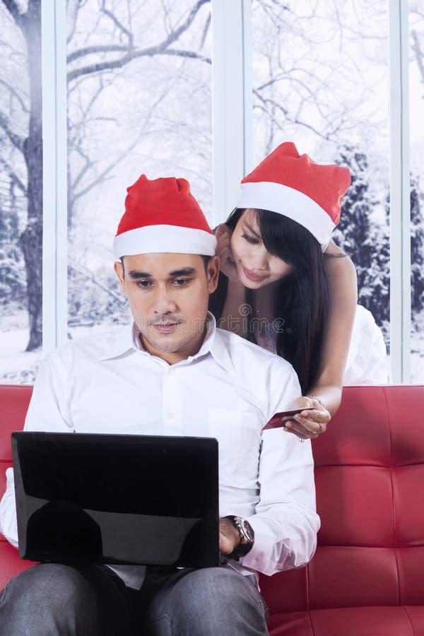 Pares jovenes que hacen compras en línea para la Navidad foto de archivo libre de regalías