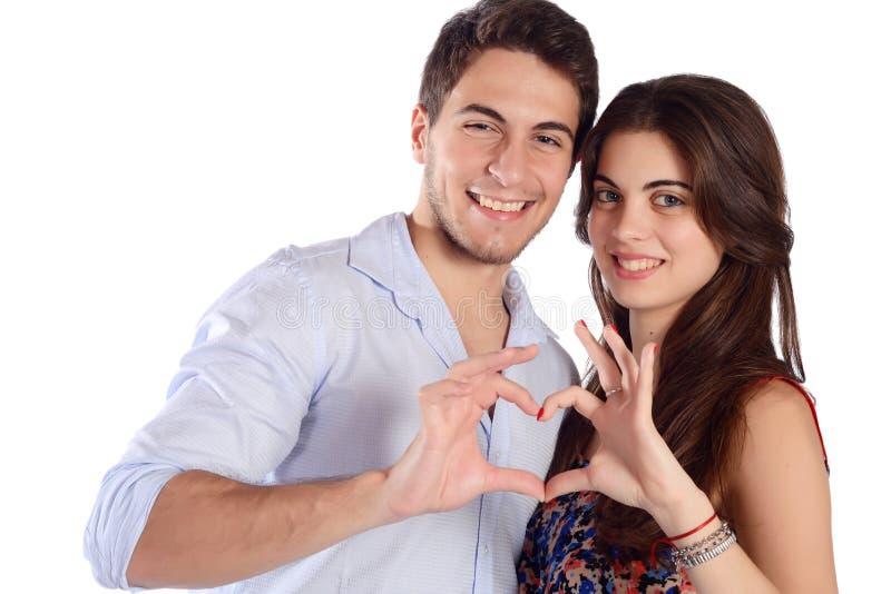 Pares jovenes que hacen dimensión de una variable del corazón fotografía de archivo libre de regalías