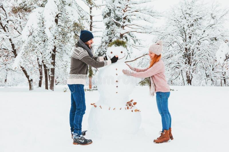 Pares jovenes que hacen el muñeco de nieve en el parque imagenes de archivo