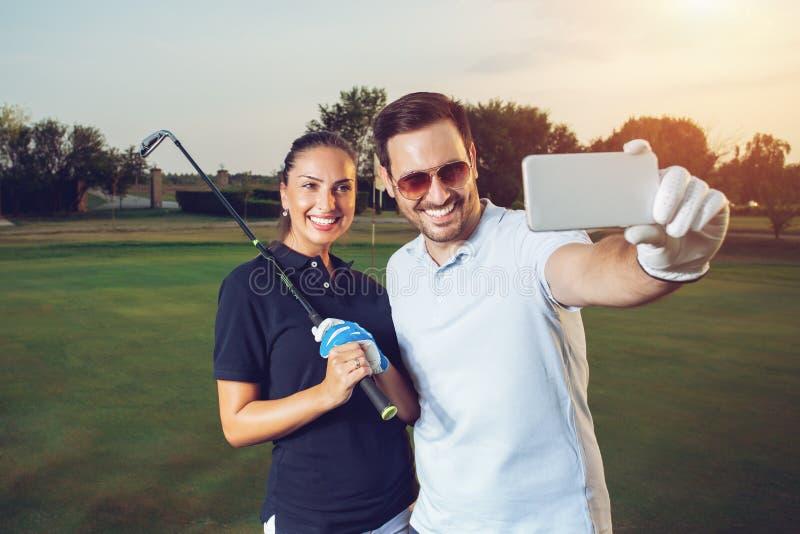 Pares jovenes que hacen el selfie en un campo de golf fotografía de archivo libre de regalías