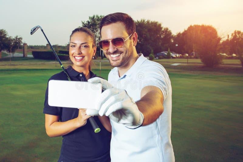 Pares jovenes que hacen el selfie en un campo de golf fotografía de archivo
