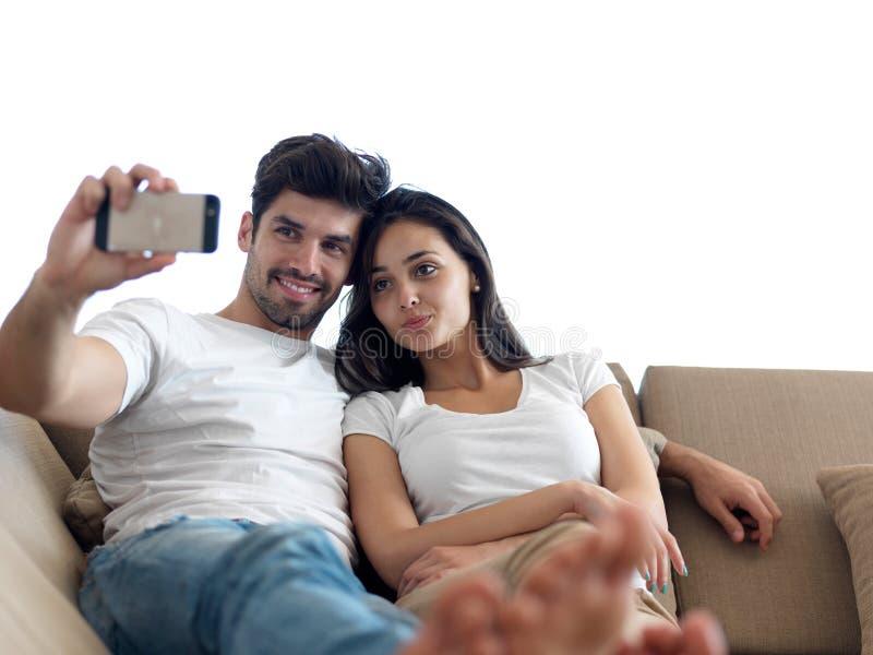 Pares jovenes que hacen el selfie junto en casa fotos de archivo