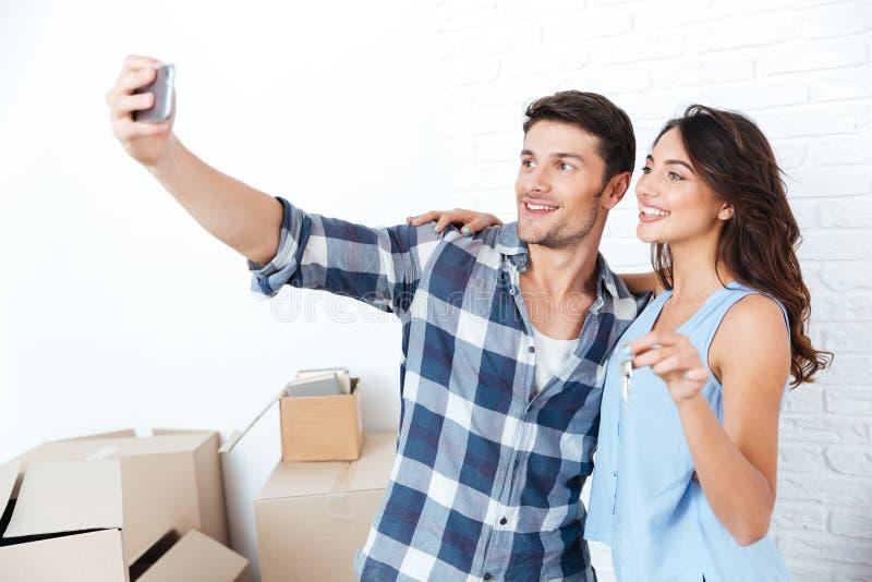 Pares jovenes que hacen el selfie que lleva a cabo llaves en nuevo plano foto de archivo