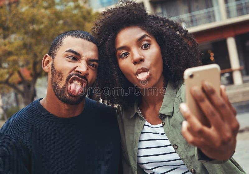 Pares jovenes que hacen la cara divertida mientras que toma el selfie en el teléfono elegante imagenes de archivo