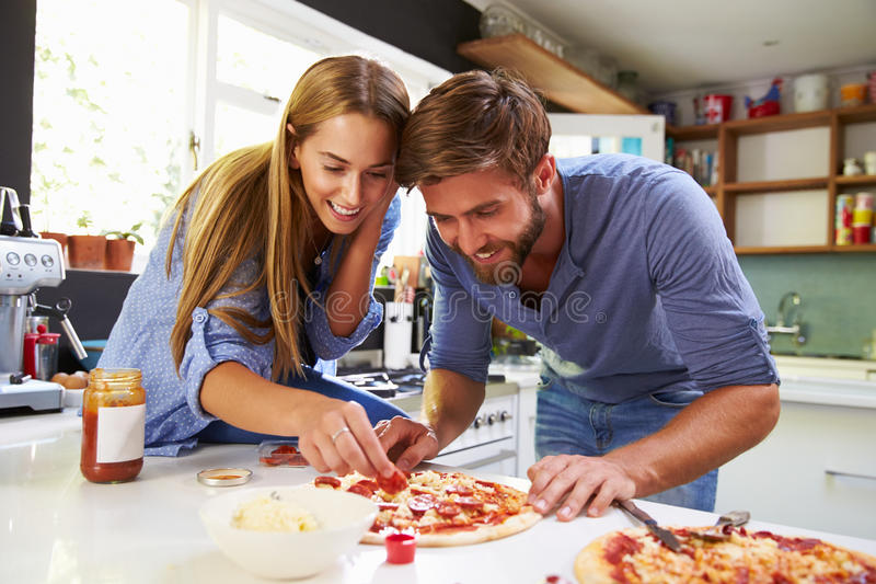 Pares jovenes que hacen la pizza en cocina junta foto de archivo libre de regalías