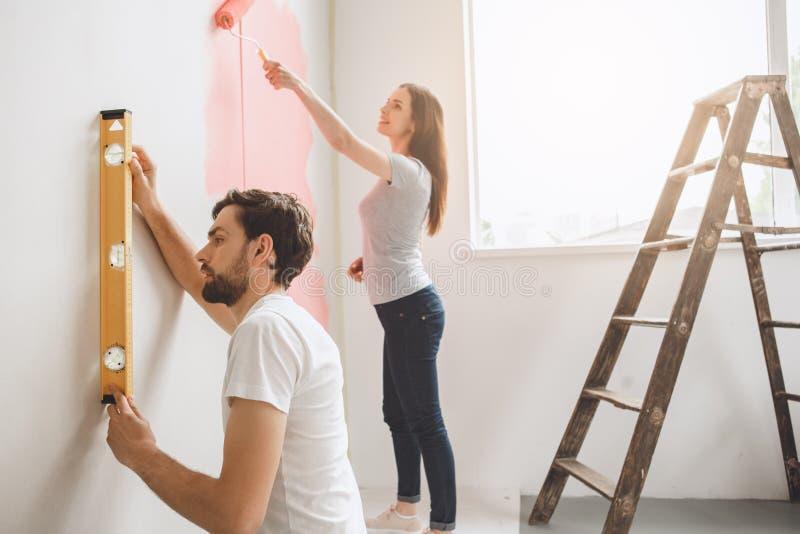 Pares jovenes que hacen la reparación del apartamento junto ellos mismos fotografía de archivo libre de regalías