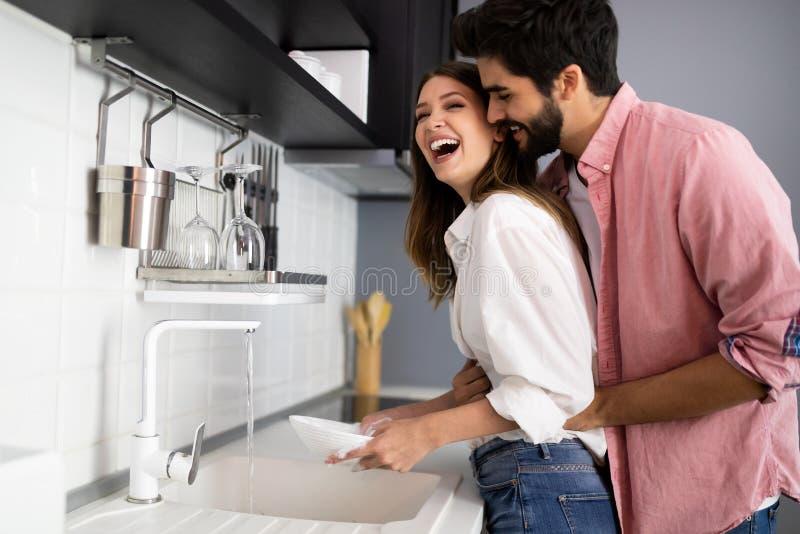 Pares jovenes que hacen platos en la cocina mientras que abraza y diviértese fotografía de archivo