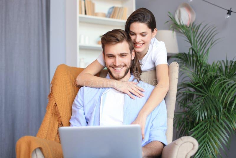 Pares jovenes que hacen un ciertas compras en línea en casa, usando un ordenador portátil en el sofá imágenes de archivo libres de regalías