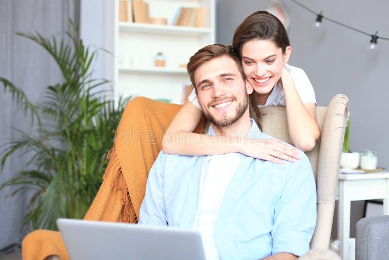 Pares jovenes que hacen un ciertas compras en línea en casa, usando un ordenador portátil en el sofá imagen de archivo