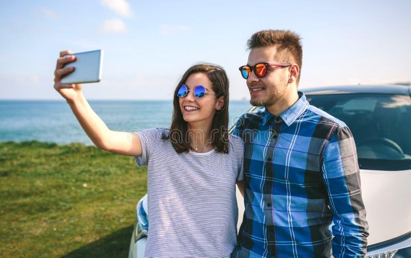 Pares jovenes que hacen un selfie en el coche imagen de archivo libre de regalías