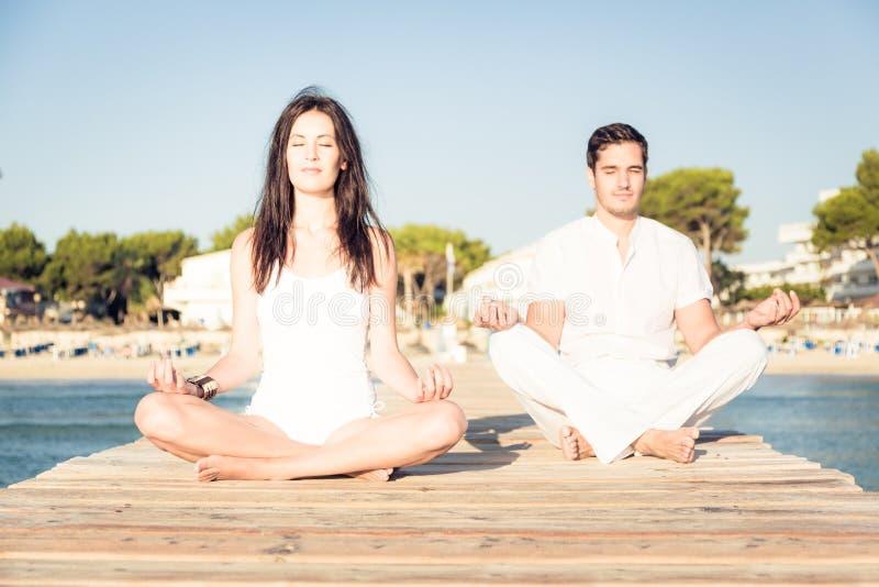 Pares jovenes que hacen yoga en el embarcadero fotografía de archivo