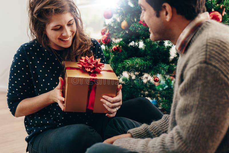 Pares jovenes que intercambian los regalos de la Navidad en casa imagenes de archivo
