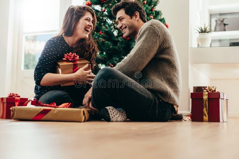 Pares jovenes que intercambian los regalos de la Navidad en casa foto de archivo