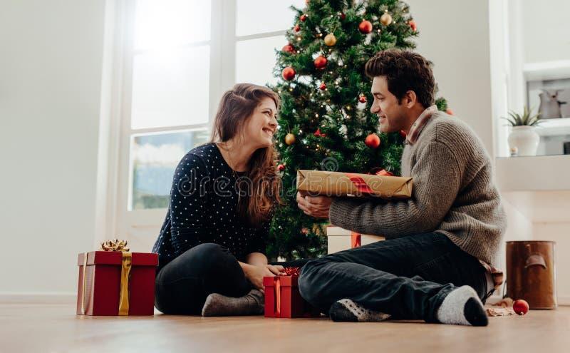 Pares jovenes que intercambian los regalos de la Navidad que se sientan al lado de un Christm fotografía de archivo libre de regalías