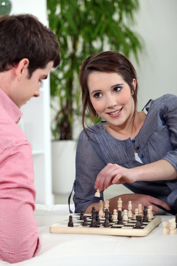 Pares jovenes que juegan a ajedrez imagen de archivo libre de regalías