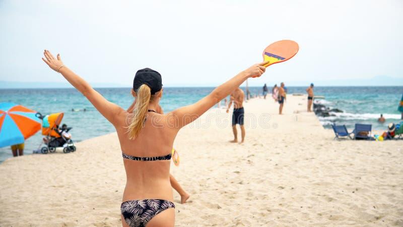 Pares jovenes que juegan al tenis de la playa que se divierte fotos de archivo