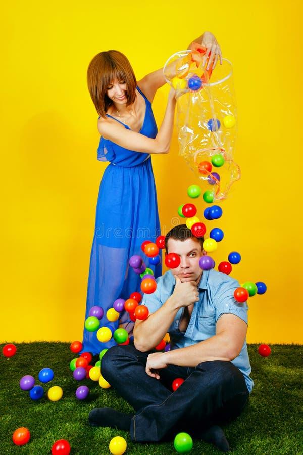 Pares jovenes que juegan con las bolas coloreadas imagen de archivo