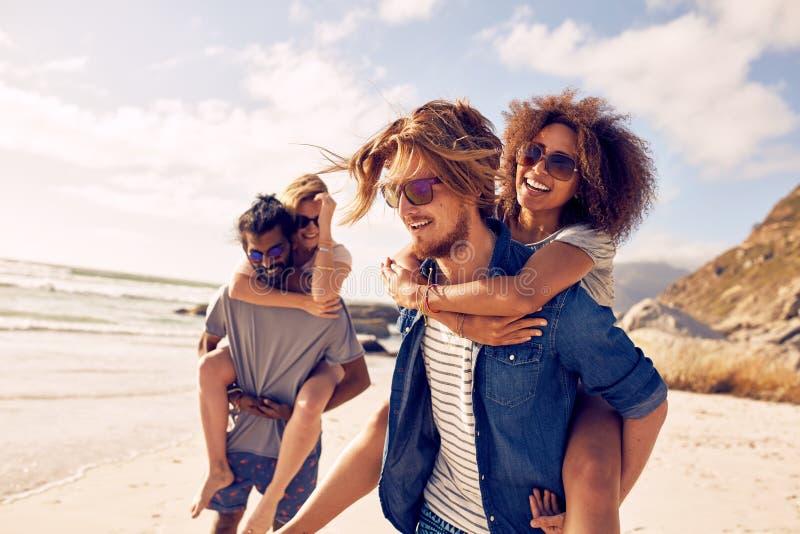 Pares jovenes que juegan a cuestas en la playa fotografía de archivo