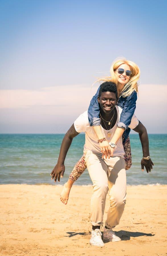 Pares jovenes que juegan en la playa - diversión con salto del transporte por ferrocarril fotos de archivo