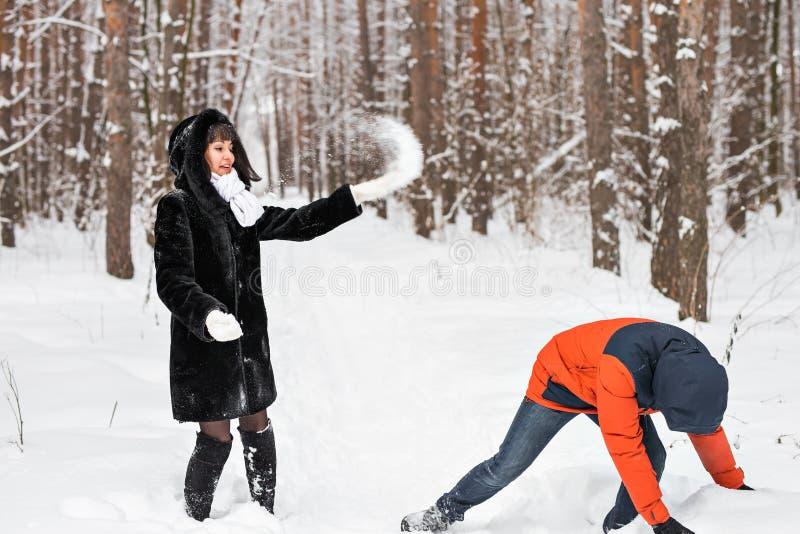 Pares jovenes que juegan en nieve, teniendo lucha de la bola de nieve fotos de archivo