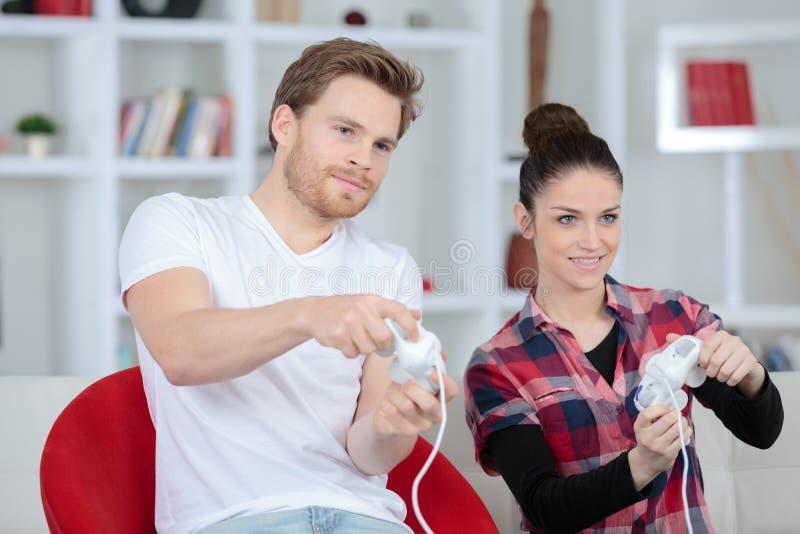 Pares jovenes que juegan a los videojuegos en su apartamento imagenes de archivo