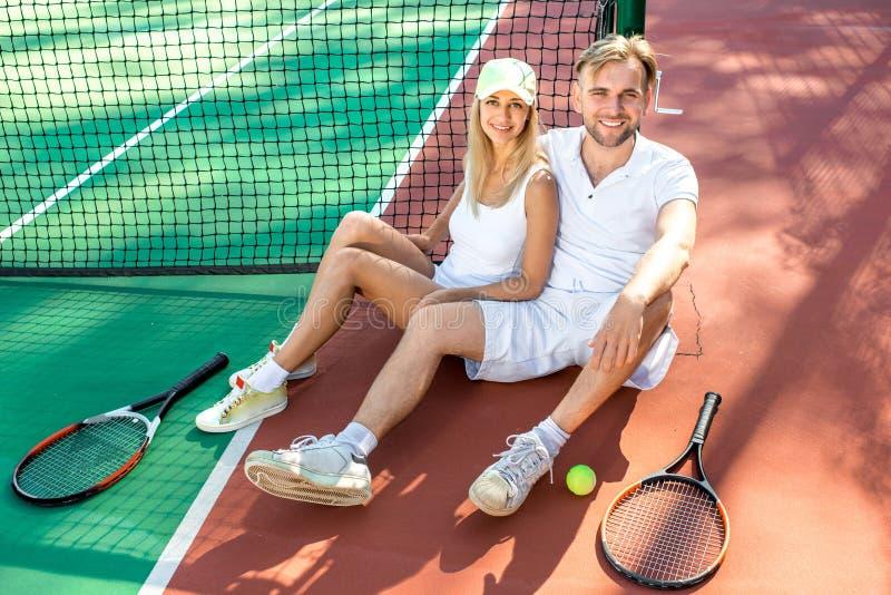 Pares jovenes que juegan a tenis foto de archivo libre de regalías