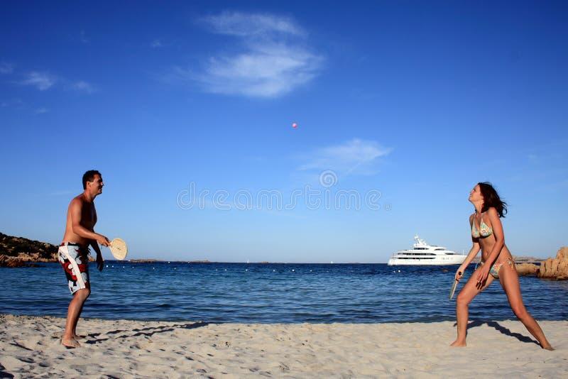 Pares jovenes que juegan a tenis en una playa. imagen de archivo libre de regalías