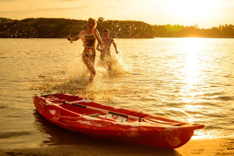 Pares jovenes que juegan y que se divierten en el agua en la playa cerca del kajak debajo del cielo dramático de la tarde en la p imágenes de archivo libres de regalías