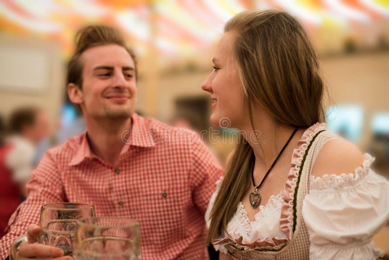 Pares jovenes que ligan en tienda de la cerveza de Oktoberfest imagen de archivo